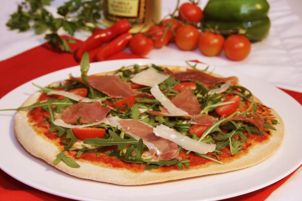 Pizza mit Rucola, Büffelmozzarella und Parmaschinken